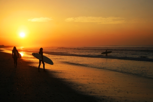 sunrise and surfers